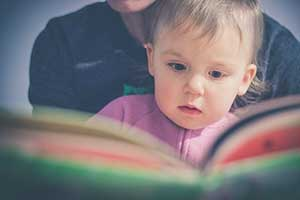 Mom reading book to toddler