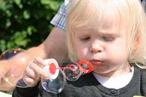 Preschooler blowing bubbles with dad